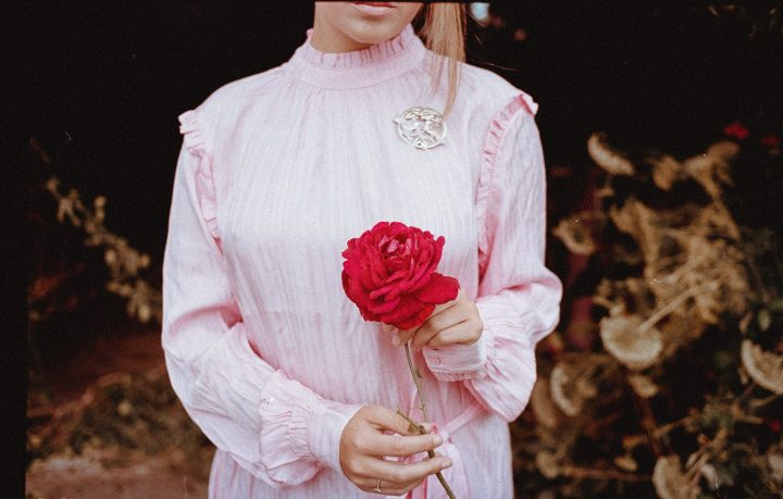 https://www.pexels.com/photo/shallow-focus-photo-of-person-in-pink-long-sleeved-shirt-holding-red-flower-3142506/