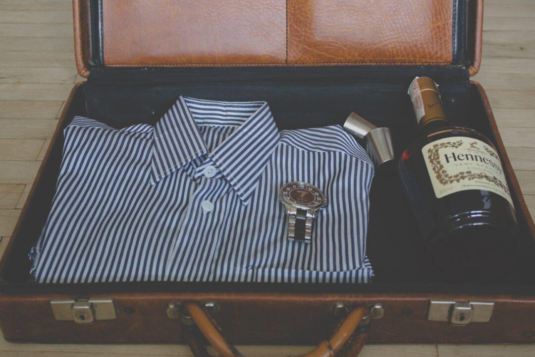 Koffer mit Hemd, Uhr und Flasche Hennessy Cognac, Photo by Angelina Litvin on Unsplash
