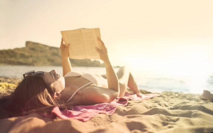 https://www.pexels.com/photo/woman-lying-on-beach-reading-book-3812741/