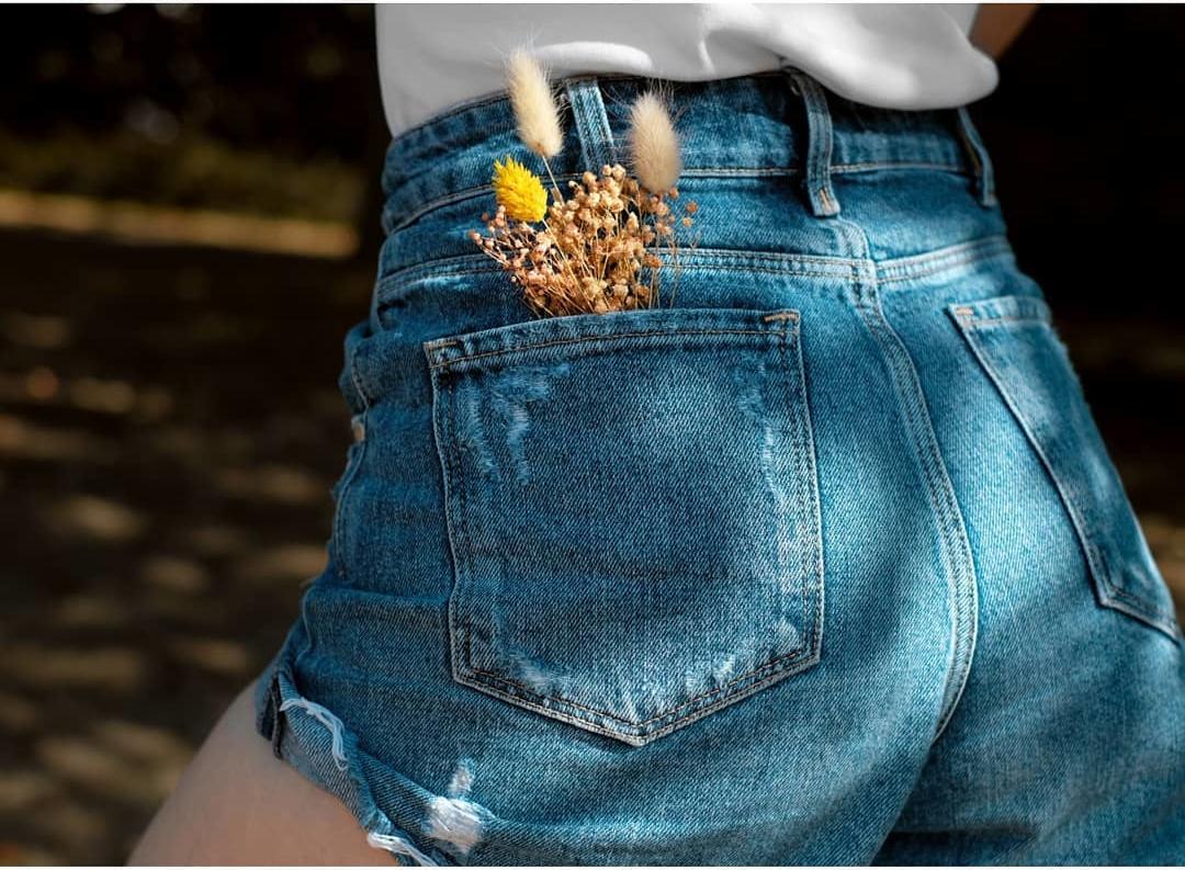 Frau in Jeans mit Trockenblumen